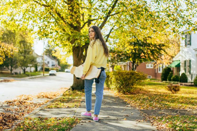 Girl with long hair holding longboard while walking on sidewalk in neighborhood looking at camera