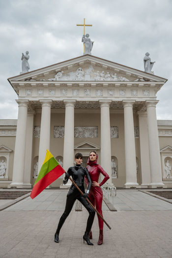 Full length of female fashion models with flag standing against church