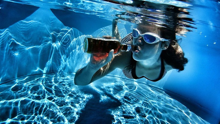 Young Woman Drinking Underwater
