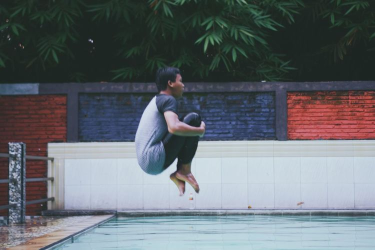 Side view of man jumping in swimming pool
