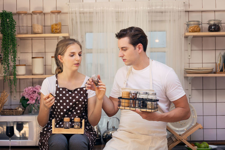 Couple with various spices talking in kitchen at home