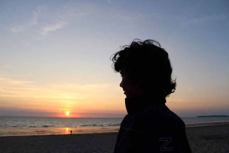 Portrait of man on beach against sky during sunset