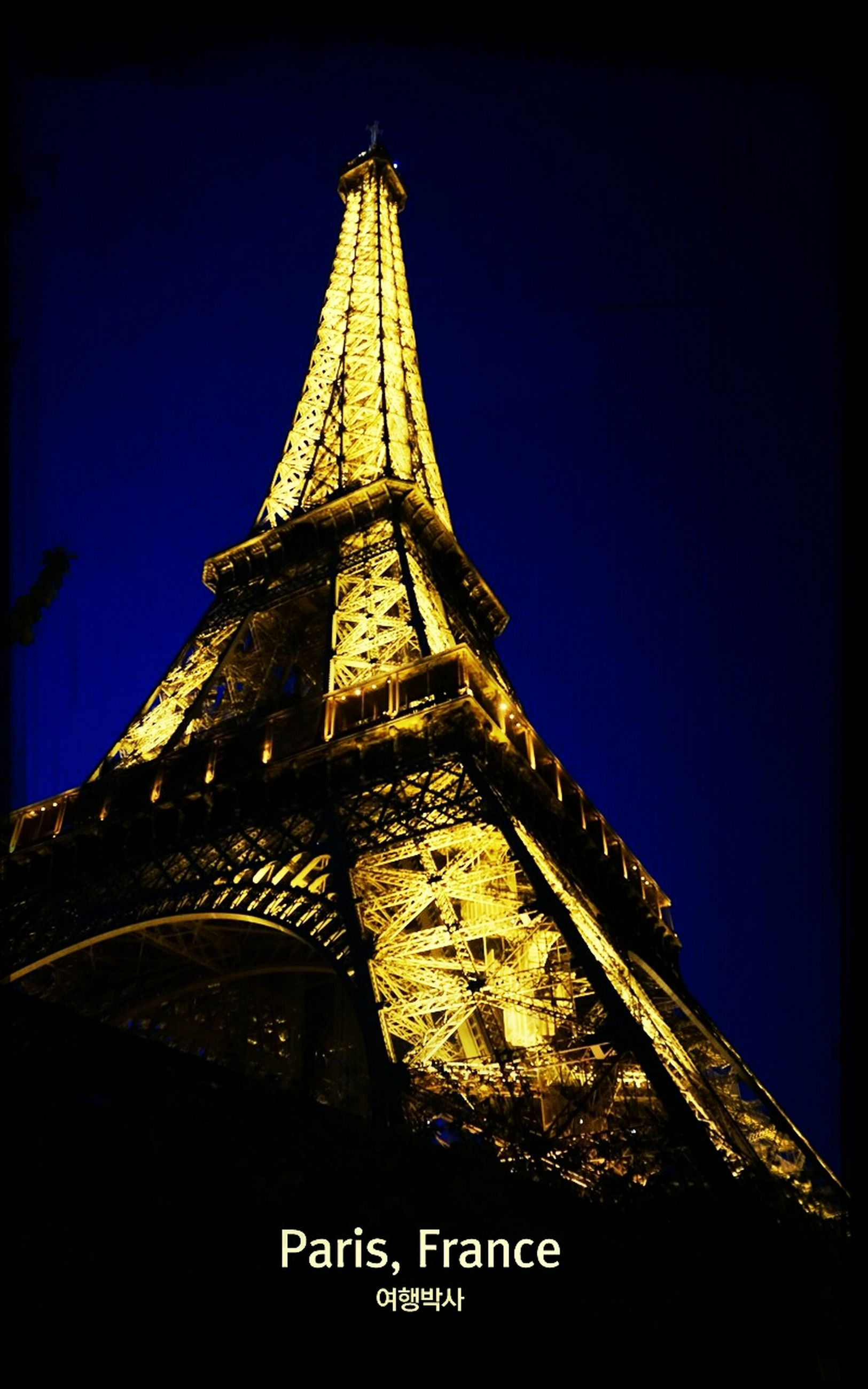 low angle view, architecture, built structure, tower, building exterior, night, clear sky, tall - high, illuminated, sky, famous place, blue, travel destinations, international landmark, auto post production filter, capital cities, transfer print, city, no people, communication
