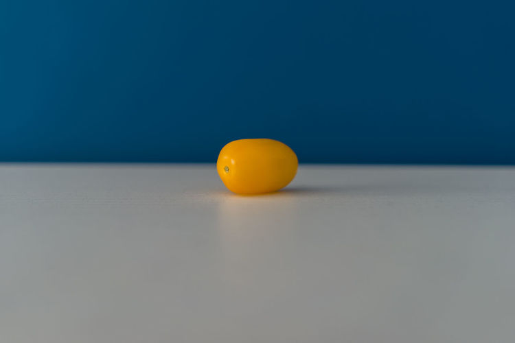 Close-up of orange ball on table against blue background