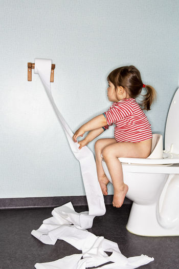 Side view of a girl sitting in bathroom
