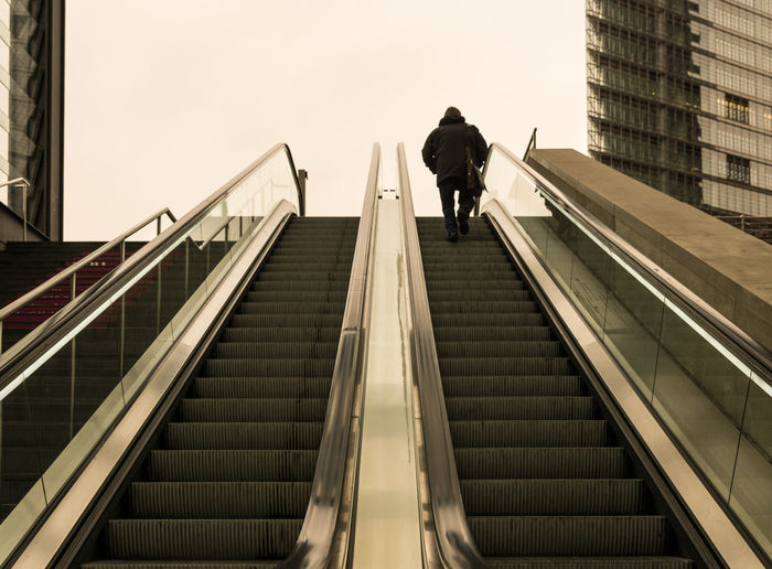 Low angle view of man on escalator against sky