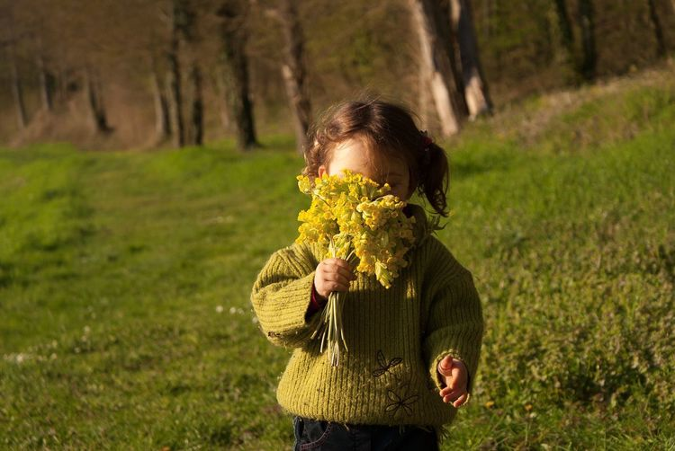 Girl Holding Flowers While Standing On Field