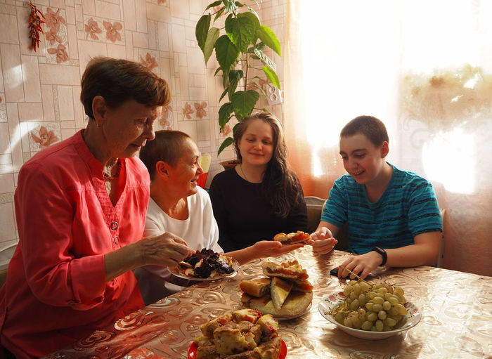 An elderly woman in bright clothes sets the table, arranges homemade cakes, prepares