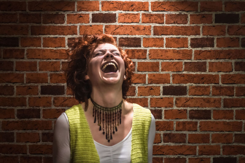 Portrait of good-lookin laughing girl with ginger curly hair and freckles looking looking at the ceiling standing over red brick wall. Photo of smiling redhead young happy lady looking camera. Attractive smiling woman portrait. Brick Wall Happy Happy People Laughing Portrait Of A Woman Adult Brick Wall Curly Hair Day Freckles Human Mouth Indoors  Laugh Laughing Out Loud Lifestyles Mouth Open One Person People Portrait Real People Screaming Shouting Young Adult Young Women