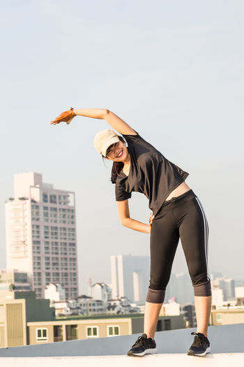 Full length of woman exercising against clear sky