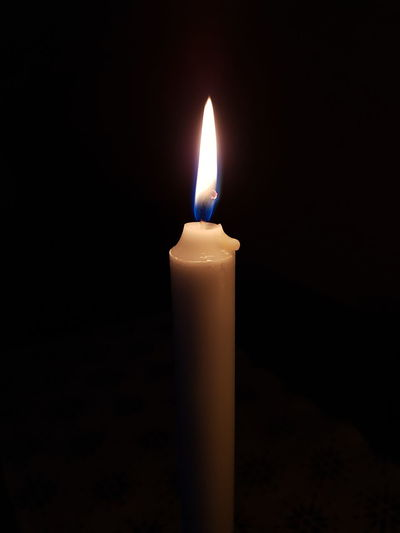 Close-up of illuminated candle in darkroom