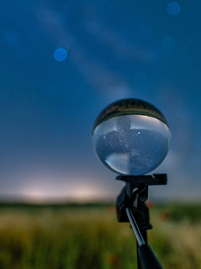 Close-up of light bulb on field against sky