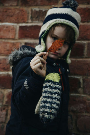 Boy holding autumn leaf against brick wall