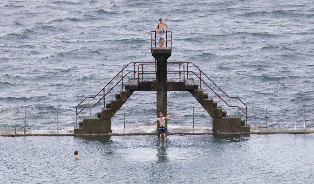 Young man jumping into seawater pool in Saint-Malo, France Aquatic Athlete Board Brittany Competition Courage Diving Board Diving Platform France Jump Jumping Mid-air Platform Pool Saint-Malo Sea Sport Swimming Swimming Pool Swimwear Training Trunks Water Young Adult Young Men