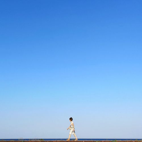 Side View Of Woman Walking Against Clear Blue Sky