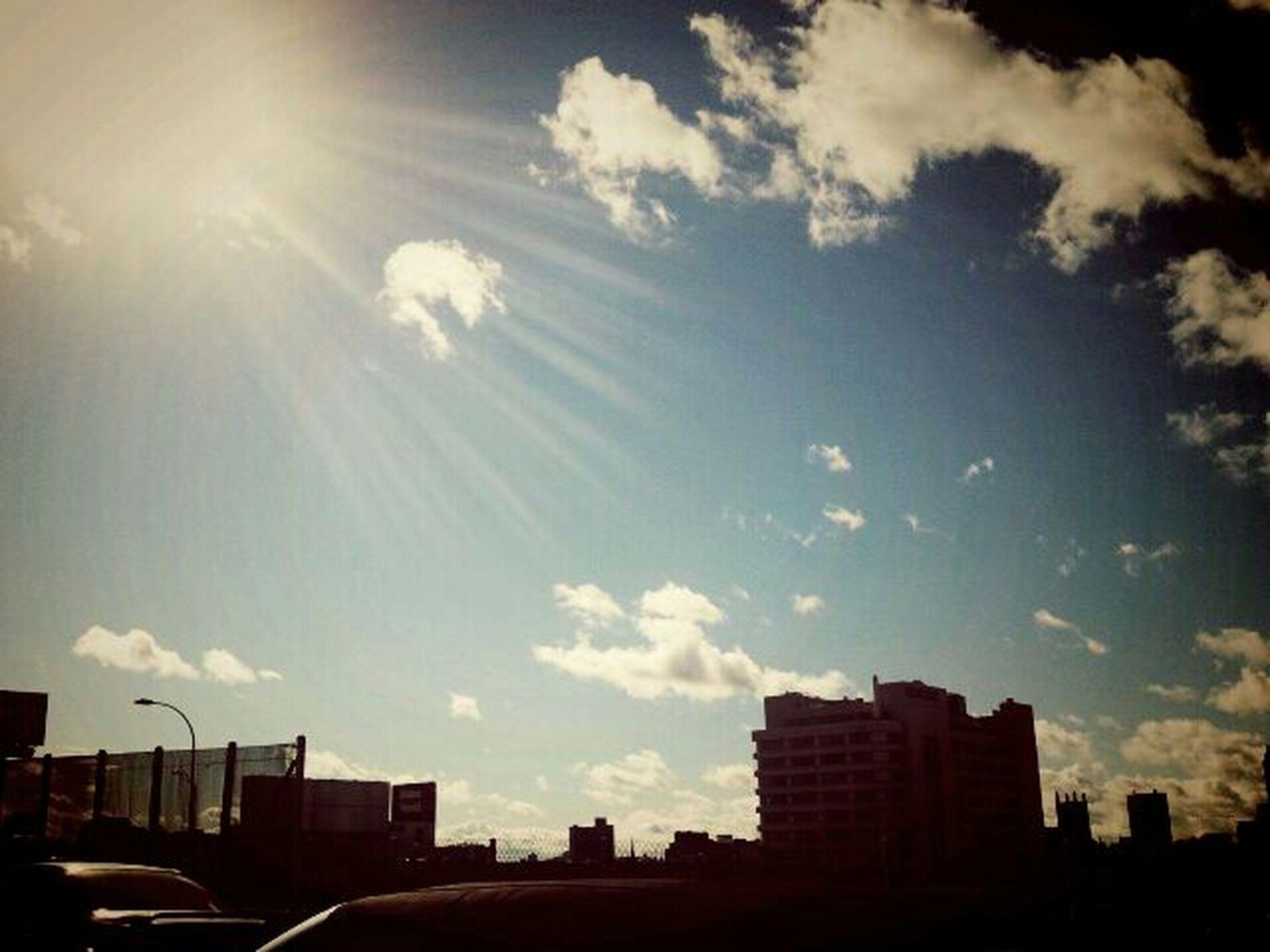 building exterior, architecture, built structure, sky, city, low angle view, sun, sunlight, cloud - sky, building, sunset, silhouette, sunbeam, cloud, transportation, car, outdoors, skyscraper, mode of transport, city life