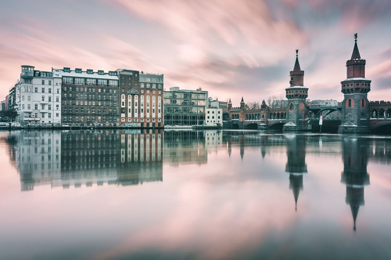 Reflection Of Oberbaumbruecke And Buildings On Spree River At Sunset