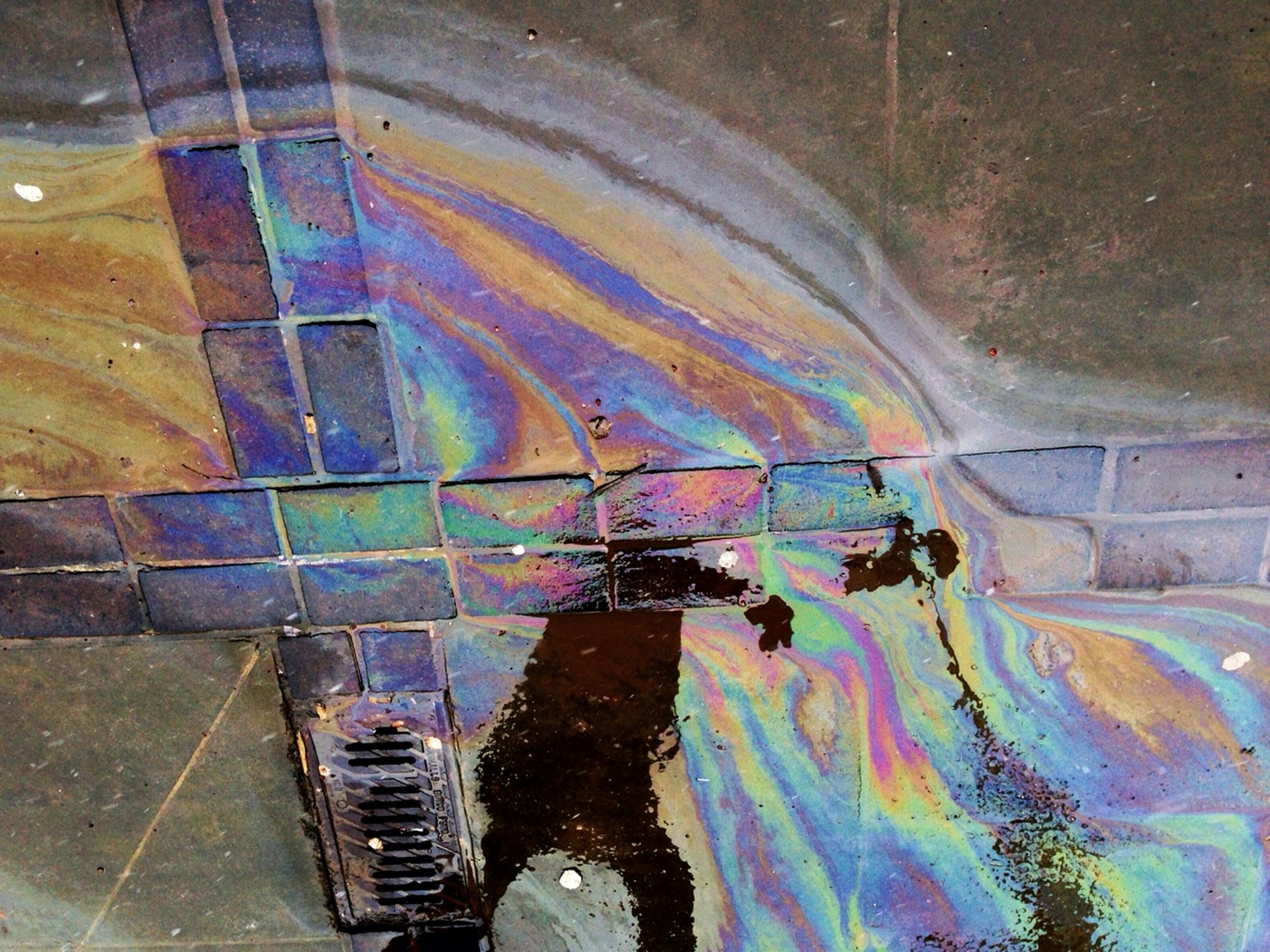high angle view, graffiti, transportation, built structure, architecture, wall - building feature, reflection, street, day, multi colored, outdoors, mode of transport, abandoned, damaged, blue, no people, water, sunlight, weathered