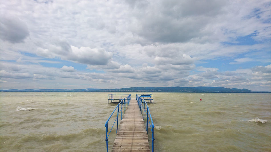 A first-person/POV shot of a pier on Lake Balaton, puffy clouds against a clear blue sky EyeEm Nature Lover Pier Travel Beauty In Nature Cloud - Sky Day Diminishing Perspective First-person Shot Horizon Over Water Jetty Nature No People Outdoors Peaceful Pov Shot Scenics Sea Sky Subjective Camera Summer Tranquil Scene Tranquility Water Wooden Structure