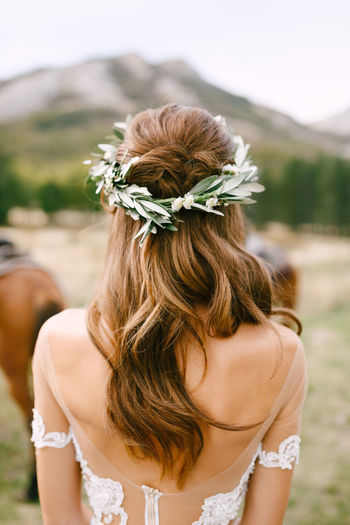 Rear view of woman wearing flowers outdoors