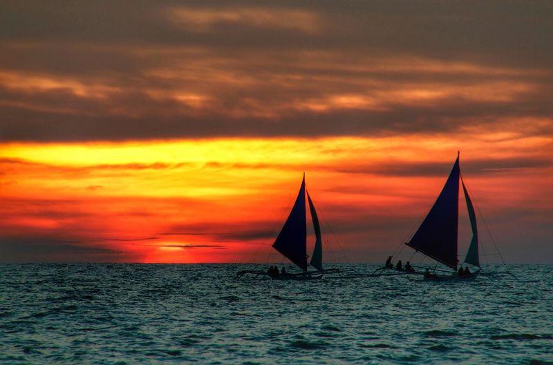 Sailboats On Sea Against Cloudy Orange Sky