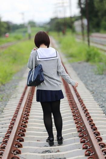 Rear view of woman in school uniform on railroad track