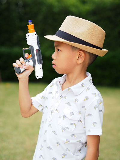 Asian boy posting with a toy gun. Portrait Outdoors Fun Asian  Asian Boy Playing Toy Guns Toys The Portraitist - 2017 EyeEm Awards