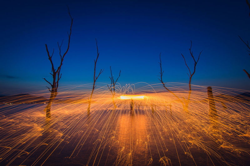 Blurred motion of illuminated land against sky at night