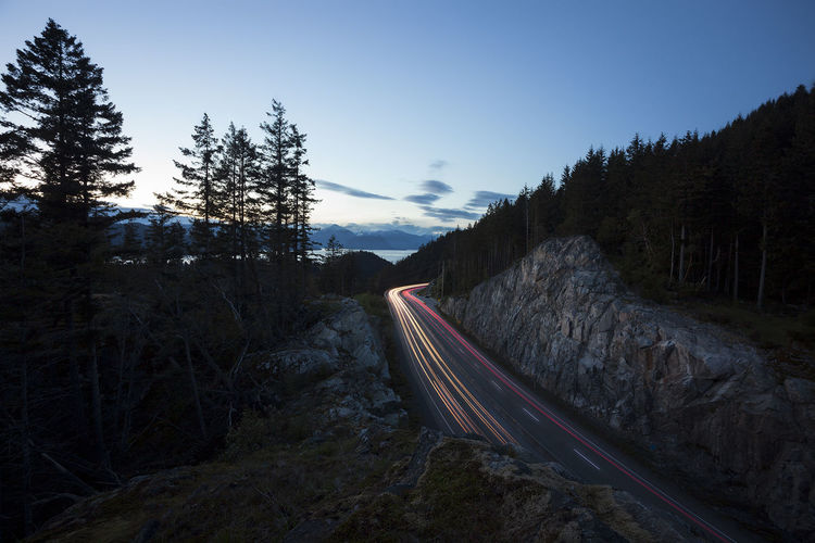 Light trails on road by mountain against sky
