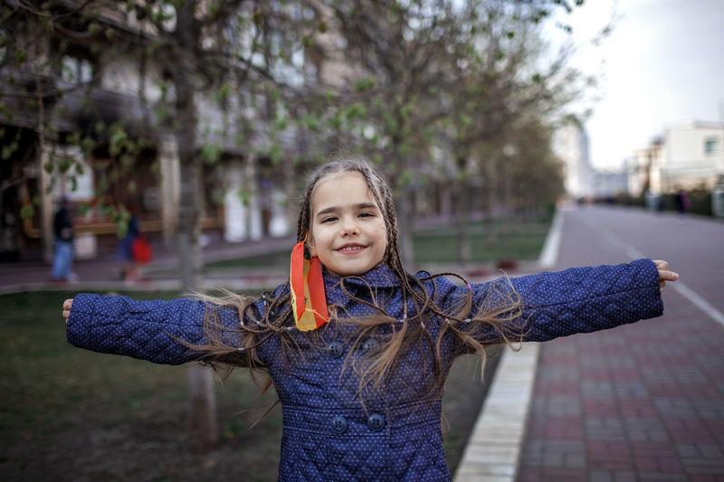 Portrait of smiling girl standing against tree