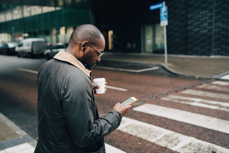 Side view of man using smart phone on street
