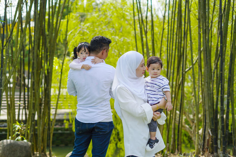 Family problem, portrait of Asian Muslim family in sadness, separation, divorce concept. Selective focus Group Of People Men Standing Togetherness Child Males  Plant Childhood Three Quarter Length Boys Family Casual Clothing Bonding Growth Love Emotion Day Positive Emotion Outdoors Son Bamboo - Plant