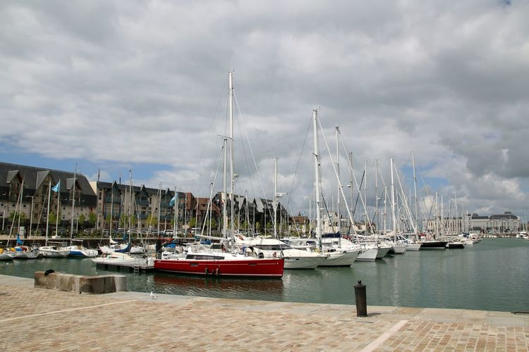 Sailboats Moored In Harbor By Buildings Against Cloudy Sky