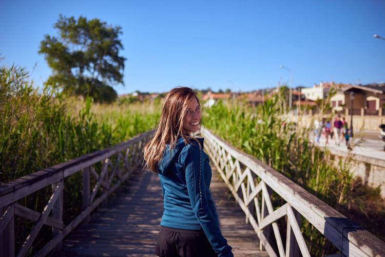 Portrait of woman standing on boardwalk by plants against blue sky