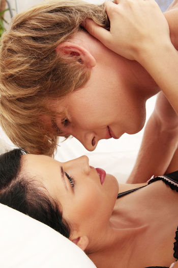 Close-up of couple cuddling on bed