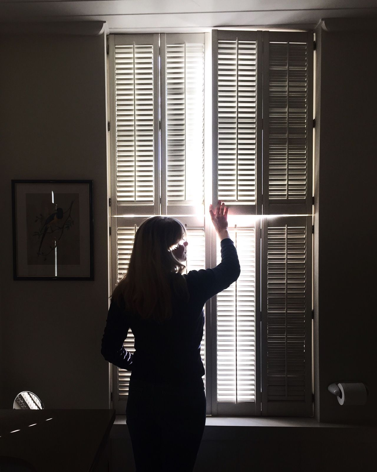 Rear view of woman holding window shutter at home
