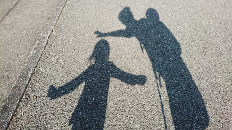 Shadow of woman with children on road