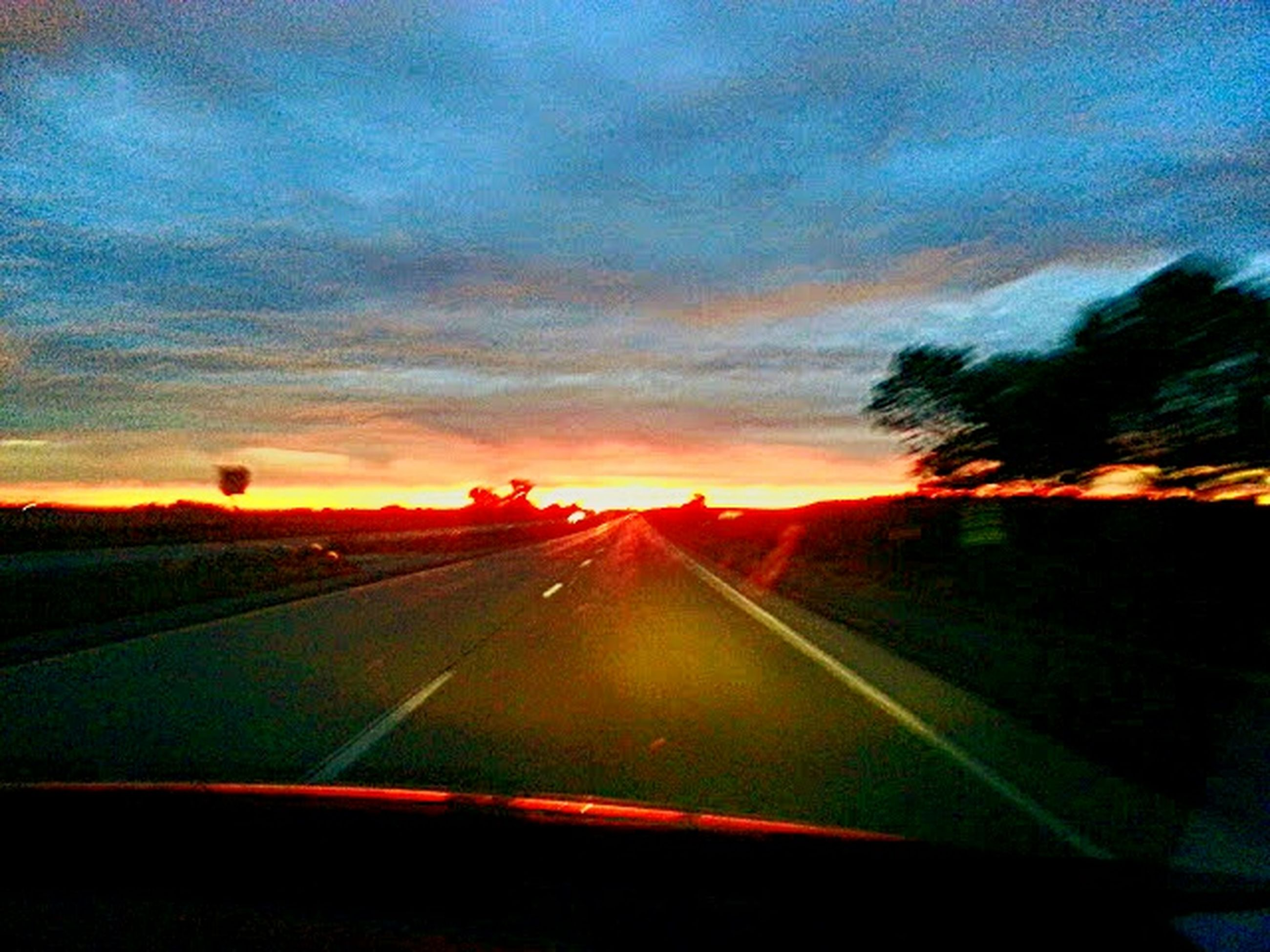 transportation, sunset, sky, road, car, mode of transport, land vehicle, cloud - sky, vehicle interior, windshield, the way forward, diminishing perspective, glass - material, transparent, road marking, orange color, car interior, travel, cloud, car point of view