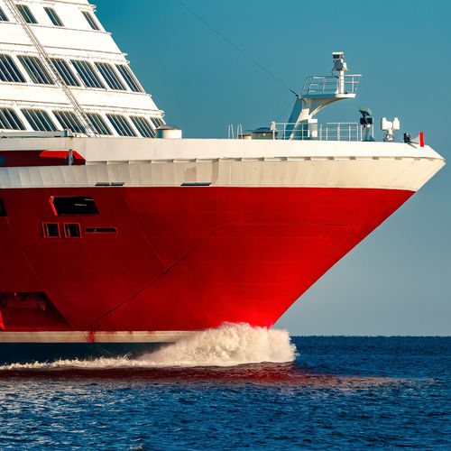 Red ship sailing in sea against clear sky
