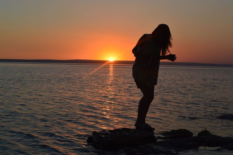 Silhouette Woman Standing On Rock Against Sea During Sunset