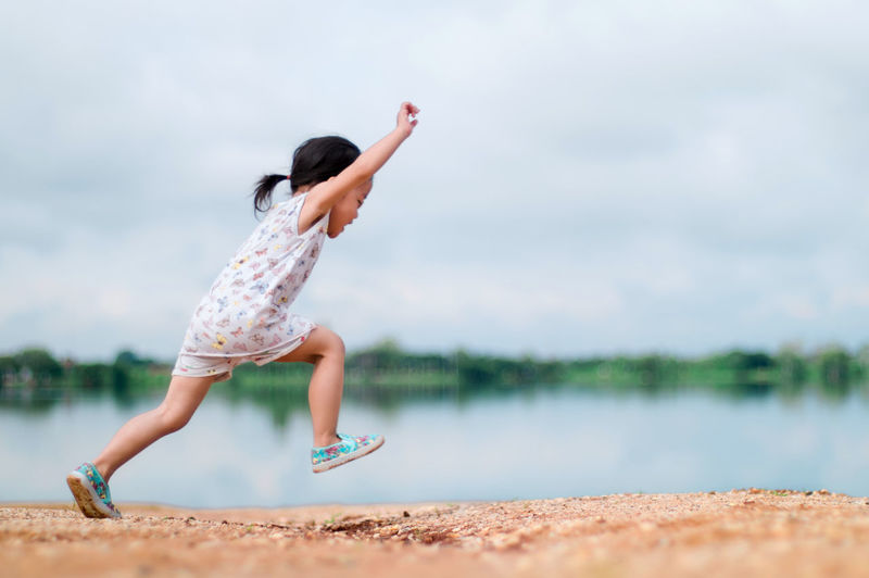 Girl running on field by river
