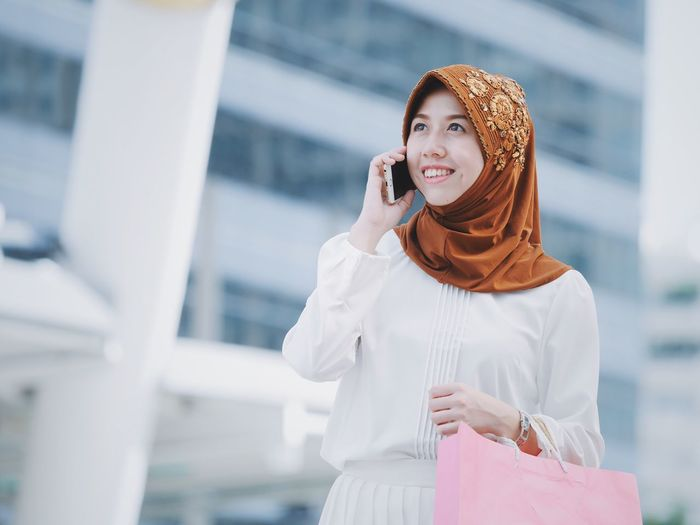 Young Woman Using Mobile Phone While Standing In City