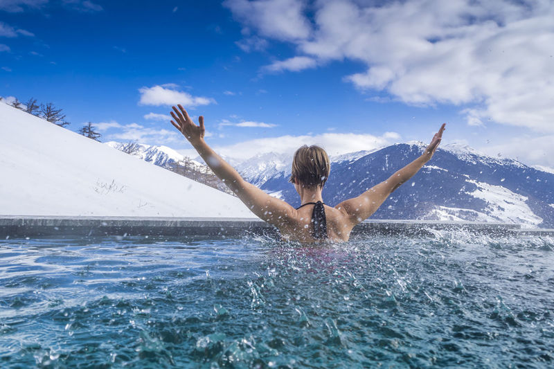 Rear view of woman with arms raised enjoying in infinity pool against mountains