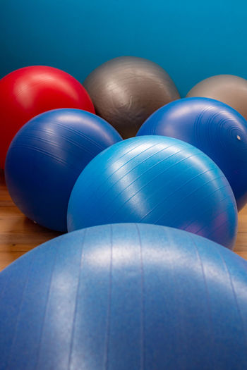 Fitness balls - many colors Blue Indoors  No People Close-up Sport Fitness Ball Still Life Multi Colored Ball Red Sphere Celebration Day Colored Background Blue Background Balloon Variation Table Pattern High Angle View Inflatable