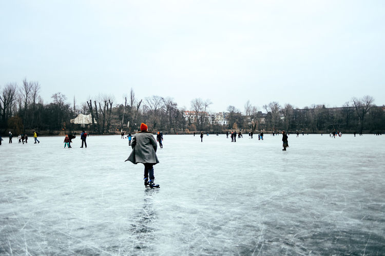 People on frozen lake against sky during winter