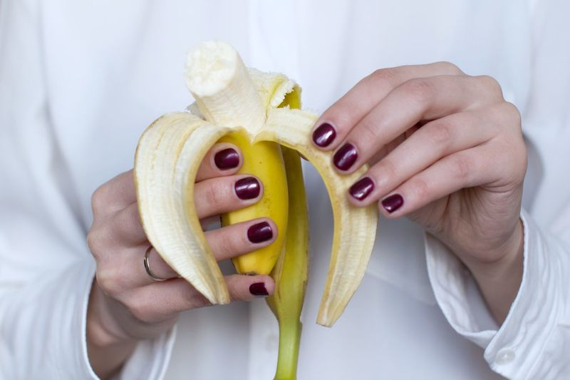 Young women in white shirt eating a banana Banana Nutrition Snack Time! Breakfast Dieting Vitamin Organic Raw Food Vegan Vegetarian Food Human Hand One Person Holding Food Women Adult Freshness Fruit Wellbeing Healthy Lifestyle Lifestyles Healthy Eating Nail Polish Eating