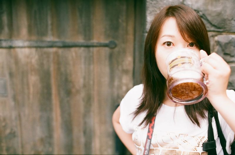 Portrait of woman drinking beer against wooden door