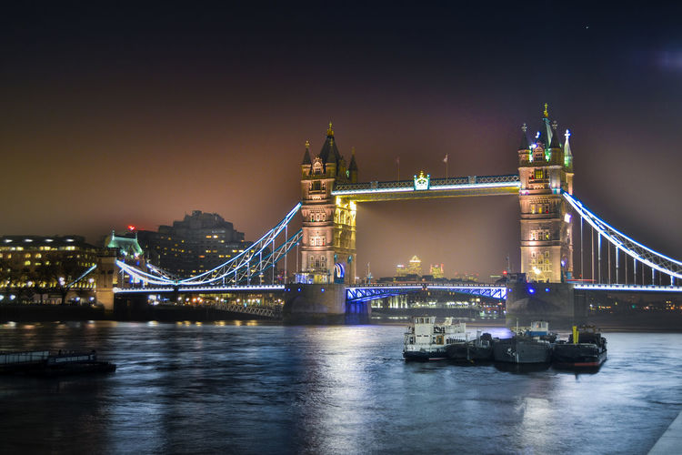 Illuminated tower bridge against sky at night