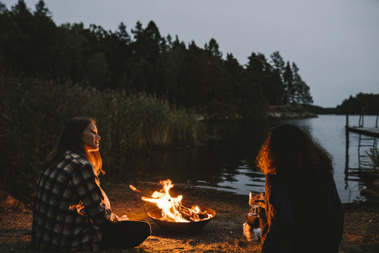 Bonfire in lake against trees