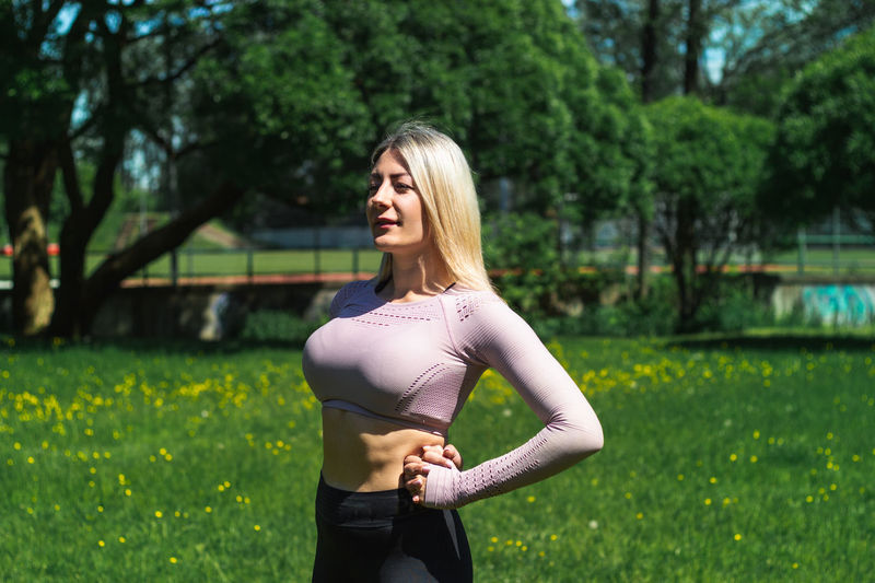 Young caucasian blond-haired woman in sportswear is doing yoga in the park. outdoor workout.